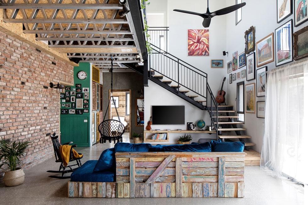 מבט מהמטבח מגלה את החומריות העשירה של הבית. מימין קיר לבן לגובה כל הבית (8 מטרים), שהפך ל''קיר אמנות''; משמאל קיר לבנים שמסתיים במבואה ירוקה לשירותי האורחים; ואחריו ארון קיר שדלתותיו עשויות תריסים ישנים, בכניסה לחדר ההורים (צילום: שירן כרמל)