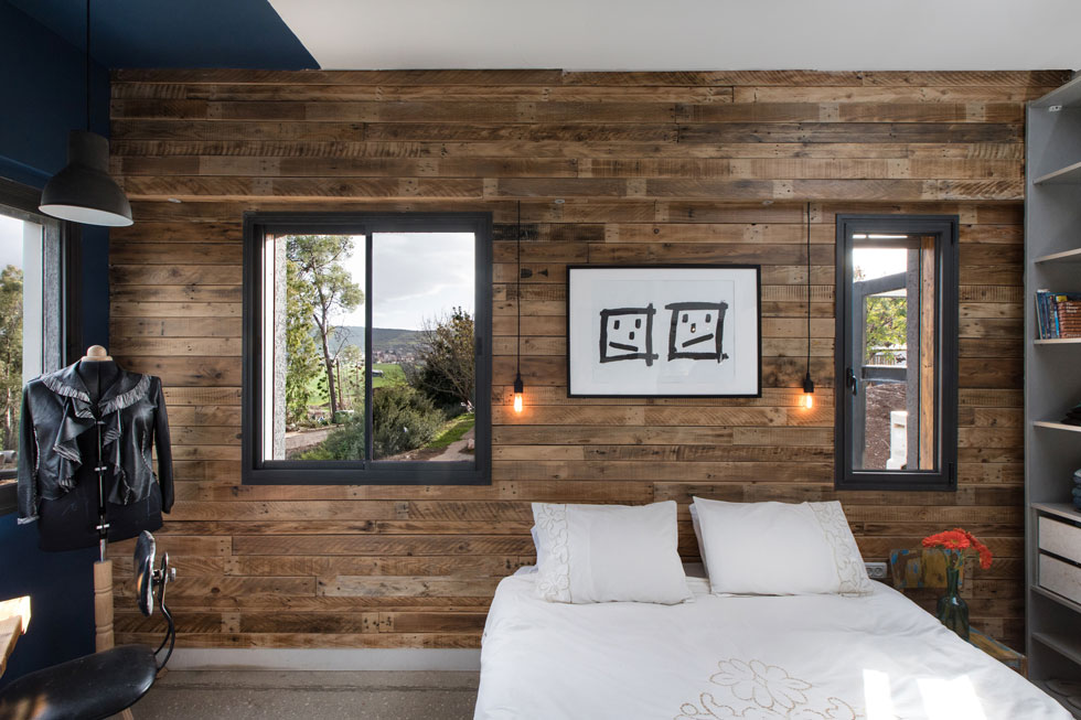 בגב המיטה קיר שכוסה בעץ כהה, ומעליה שרבוט גרפי של עופר (צילום: שירן כרמל)