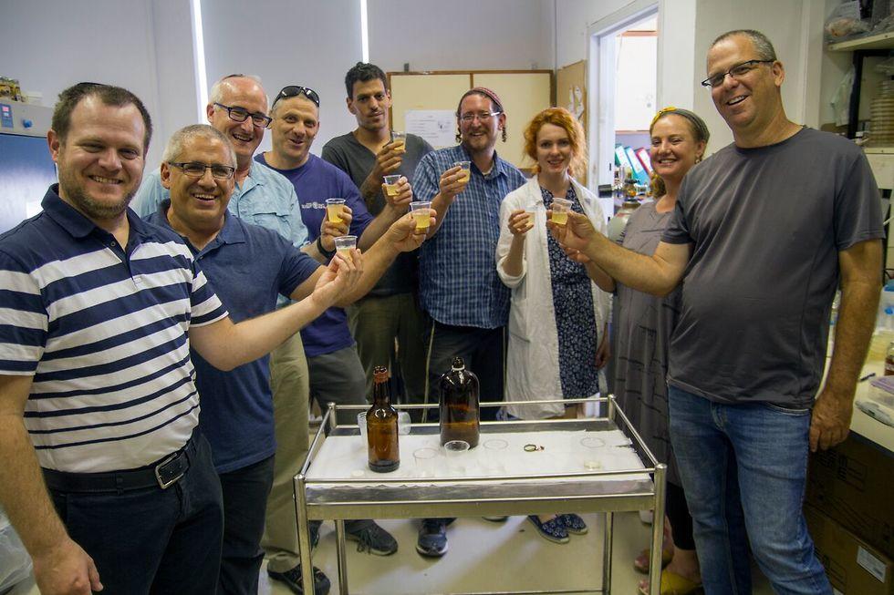 צוות החוקרים עם בקבוקי הבירה החדשה-ישנה שיוצרו במעבדות (צילום: יניב ברמן, באדיבות רשות העתיקות)