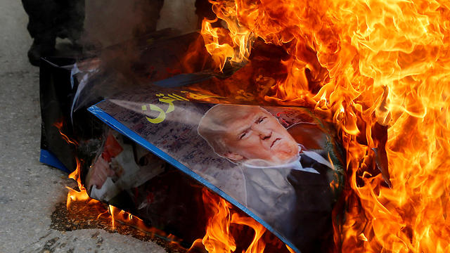 Protesters burn a photo of US President Trump