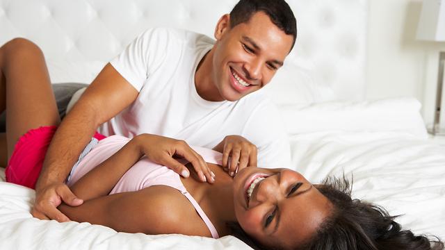 זוג צוחק במיטה (צילום: Shutterstock)