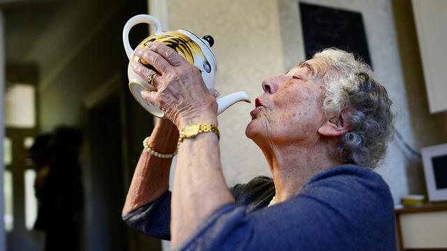 Judith Kerr drinks from a tea pot as she recreates a scene from her bestselling picture book 'The Tiger Who Came To Tea,' at her home in west London, Britain September 30, 2015