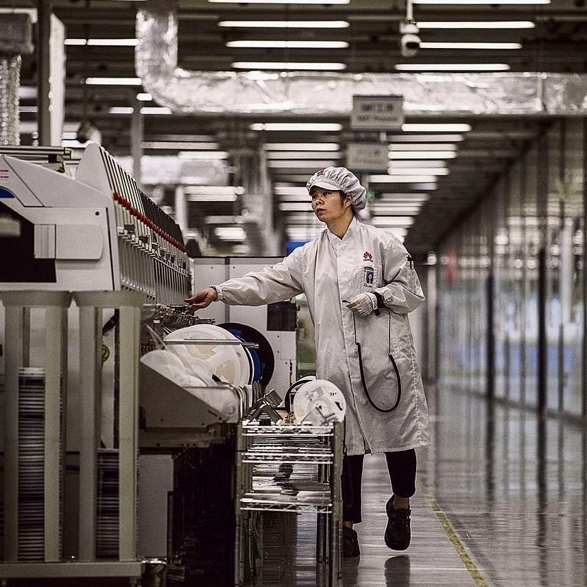 עובדת אוספת סמארטפונים של וואווי בסוף קו הייצור. העובדים מקבלים דיור זול במתחם