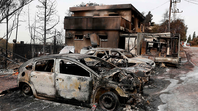 Cars and homes burned in Mevo Modi'im (Photo: AFP)