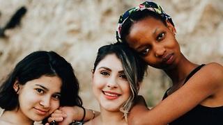 שלוש נשים מחובקות ומחייכות  ()