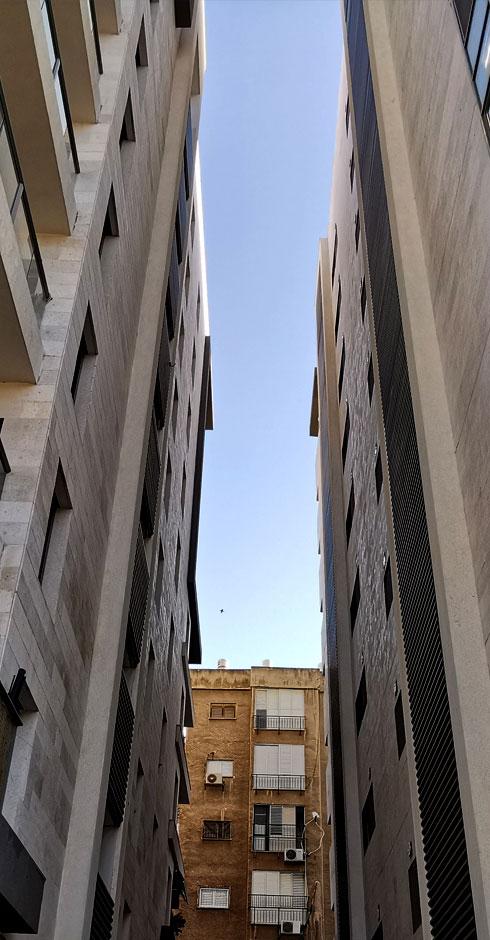 מישהו אמר חמצן? שני בניינים שעברו תמ''א של הריסה ובנייה ברחוב אביגיל, וביניהם נדחק הגב של בניין ישן, שחזיתו פונה לרחוב ביאליק הסואן  (צילום: נעם רוזנברג)