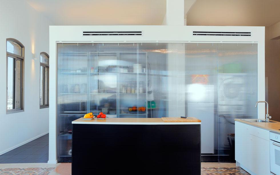 """בין המטבח למרחבים הפרטיים מפריד קיר גבס בצורת ח', מכוסה """"וילון"""" פוליגל שקוף, עם יחידות מידוף מברזל, שבני הזוג הרכיבו בעצמם: משמאל אחסון שמשרת את המטבח, ומימין לעמוד - מעין ארון שירות עם מקרר, מכונת כביסה ומייבש  (צילום: נור עבדלגני)"""