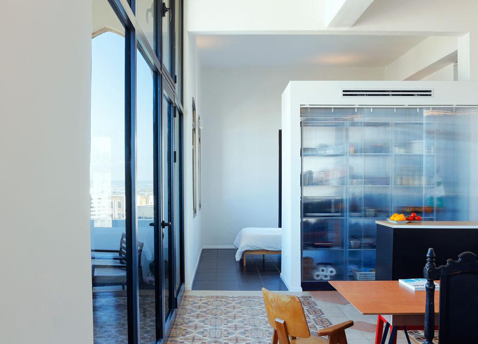 """חדר ההורים, ללא דלת, נמצא מאחורי מחיצת הגבס. """"תכננו את הדירה למה שנכון עכשיו. אם בעתיד זה לא יתאים - נסגור, או נעבור לדירה אחרת"""", אומרת מיטל. בחדרי השינה הוחלף הריצוף המקורי באריחים אפורים  (צילום: נור עבדלגני)"""