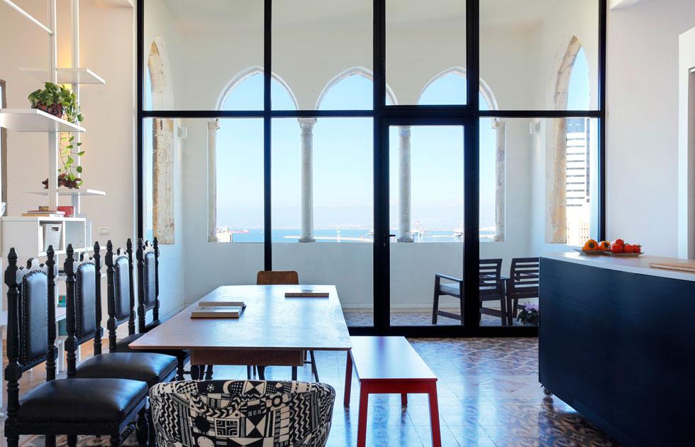 הקמרונות היפים של החלונות האלה, בחיפה תחתית, היו מכוסים בקיר. בני הזוג חשפו אותם, החזירו את המרפסת לתפקידה המקורי והפרידו בינה לבין המרחב המרכזי של הדירה בעזרת ויטרינות. עיצוב: בריזה אדריכלים. לחצו לכתבה המלאה (צילום: נור עבדלגני)