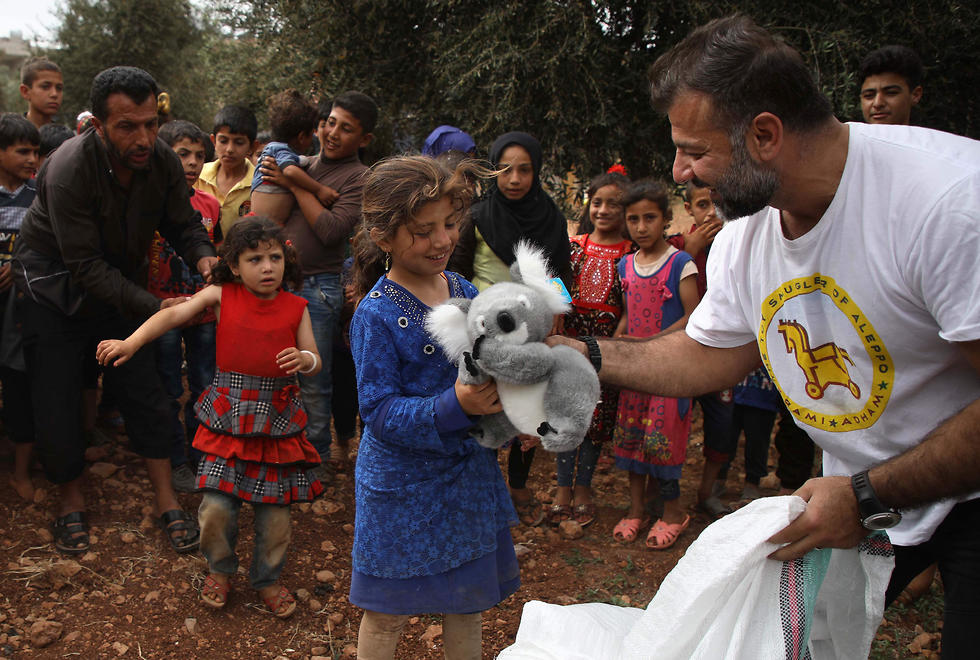 A Syrian living in Finland distributing toys to children at a refugee camp in Idlib province