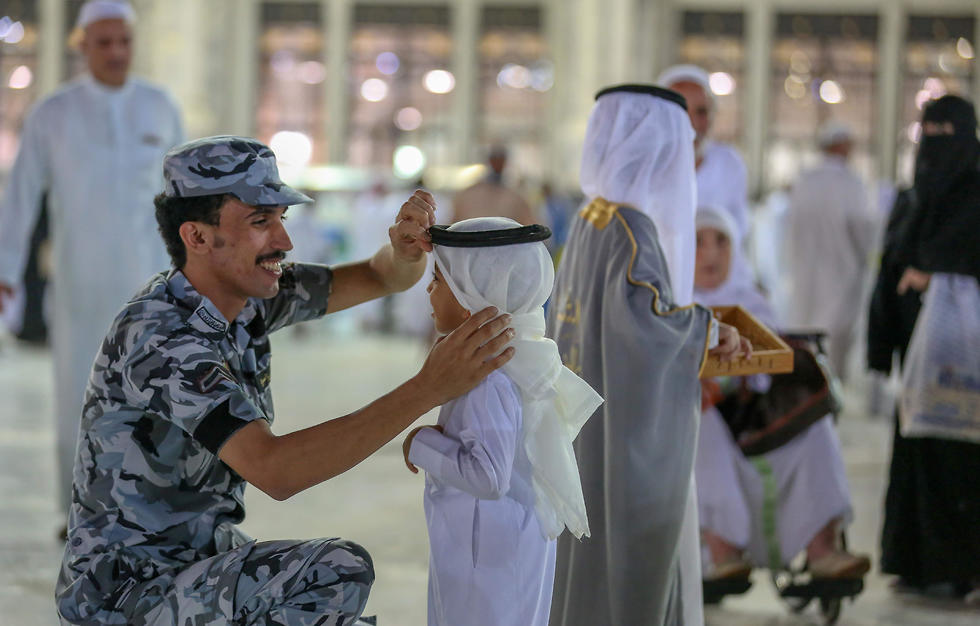 A security officer fixes the headscarf of a child at Mecca's Grand mosque