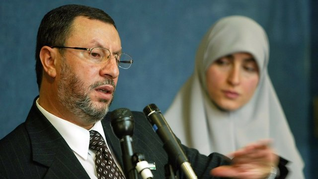 Abdelhaleem Ashqar, left, with his wife Asma, right, meets reporters in 2004