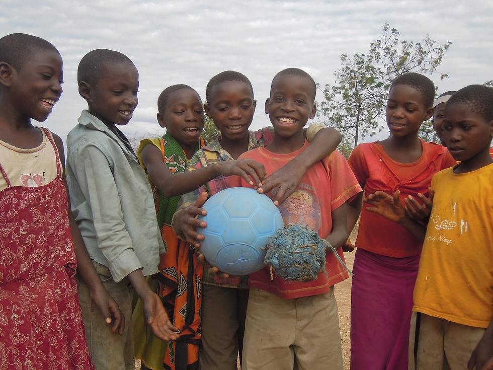 ילדים אפרחקנים אוחזים בכדור סמרטוטים לצד כדורגל חדש (צילום: AFRICAGOAL)
