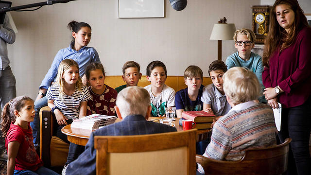 Albert Gomes de Mesquita and Jacqueline van Maarsen talk to students of the Anne Frank Montessori school on the famed Holocaust diarist's 90th birthday in her former home in Amsterdam, June 12, 2019