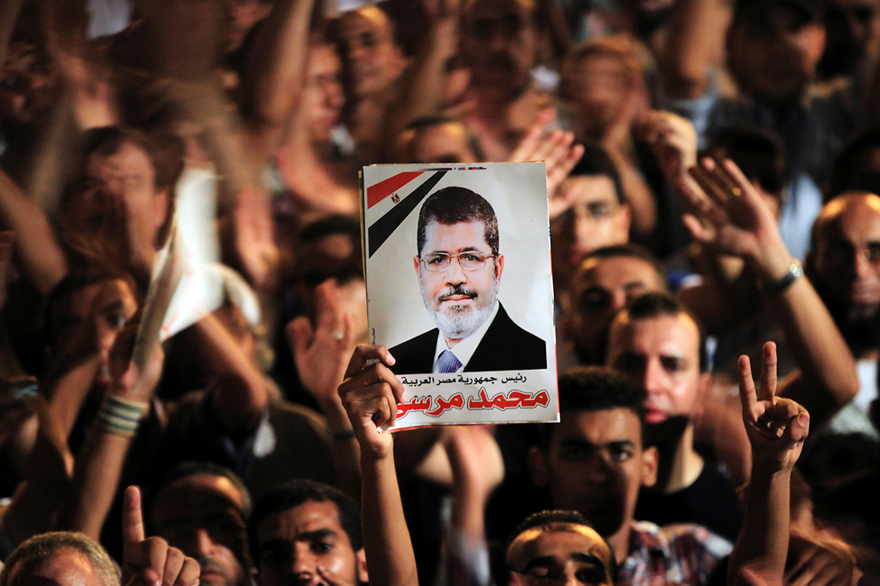 Morsi supporters hold photos of the former president during a protest in Cairo's Tahir Square in 2012 (Photo: Reuters)