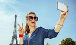 אישה מחזיקה סמארטפון ליד מגדל אייפל (צילום: shutterstock)