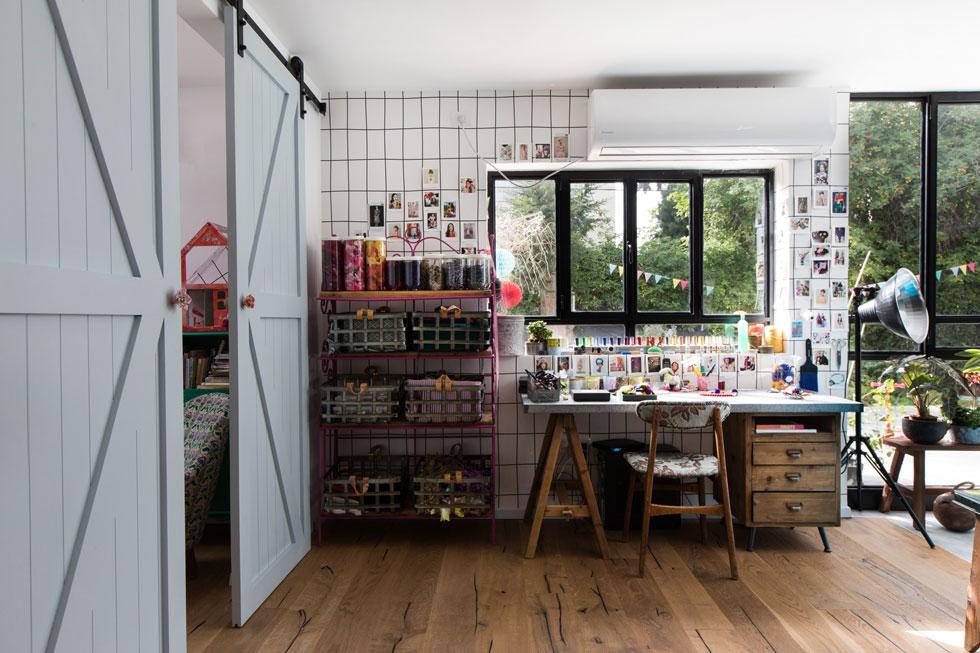חומרי הגלם מוצגים לראווה בקופסאות ובסלסלות. לצדן שולחן עבודה ישן מעץ, עם כיסא וינטג' שגרטנברג ריפדה בעצמה (צילום: שירן כרמל)