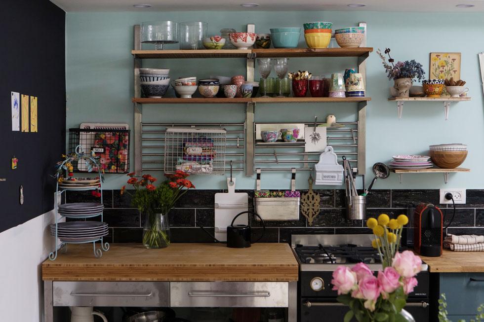 שלוש שורות של אריחים שחורים נותרו משיפוץ קודם, ועל המדפים הפתוחים כלי אוכל צבעוניים (צילום: שירן כרמל)
