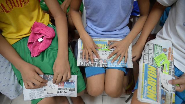 Israeli-born Philippine children reading news articles (Photo: AFP)
