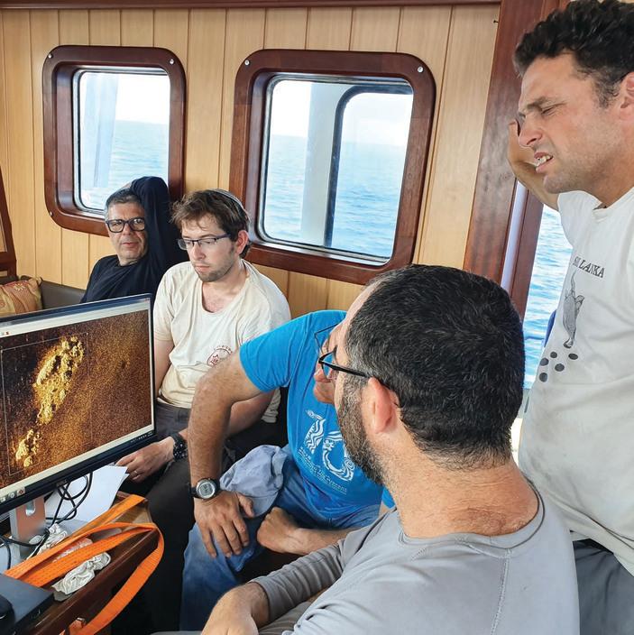 """משמאל: פרופ' גרופר,  שמואל כהן, קובי שרביט,  בן הרצברג וד""""ר דיאמנט (עומד) צופים בתמונה שתיעד הרובוט בקרקעית הים"""