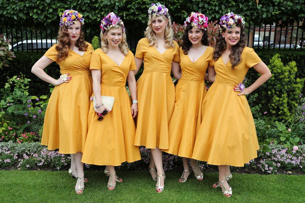 חברות להקת הבנות הטוטסי רולרס, בשמלות וינטג' תואמות בצבע חרדל מבוטיק Collectif Clothing וכובעים פרחוניים של המעצבת קליאה ברוד (צילום: Chris Jackson/GettyimagesIL)