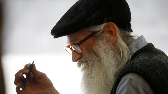 Michael Netzer sketches a passerby on a bench in Jerusalem on June 12, 2019