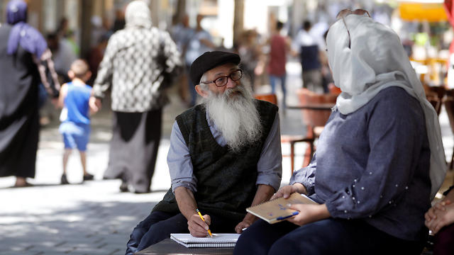 Michael Netzer sketches Endy Jber, 24, a conservative Muslim woman from the Arab village of Abu Ghosh, on a bench in Jerusalem on June 12, 2019