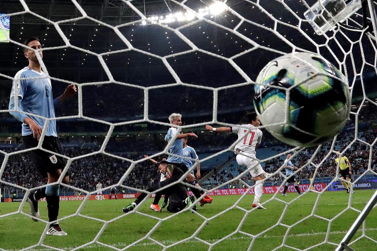 הכדור של מיושי נוחת בשער של אורוגוואי (צילום: EPA)