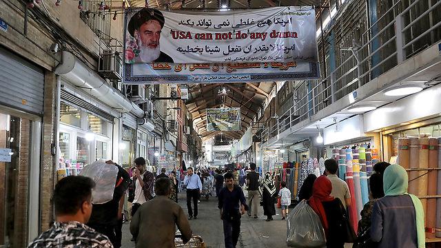 An image of Ayatollah Khamenei hands in the main bazaar in Tehran