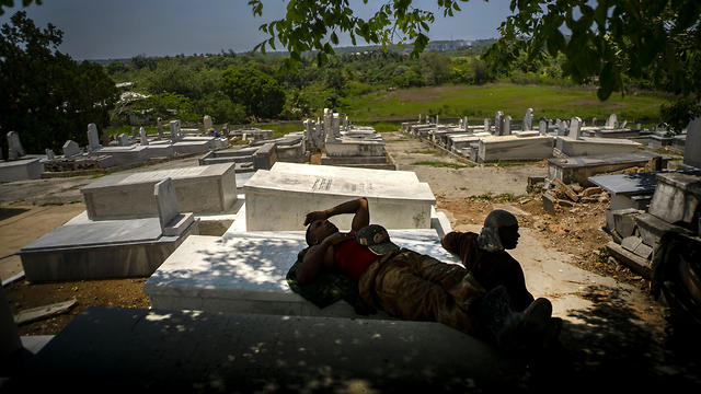 Workers repairing the Jewish cemetery take a break in the shade (AP)