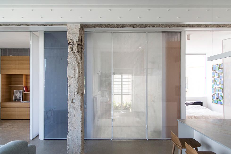 """דירה בתכנון מיליק הראל אדריכלים. מחיצה בת שלושה חלקים מפרידה, לכל האורך, בין החלק הציבורי לפרטי. """"הרעיון היה"""", מסביר האדריכל אורי מיליק, """"לאפשר חיבור של החדרים והחלל המרכזי בפעולה פשוטה, כך שמתקבלת הרגשה של לופט, של מרחב פתוח ככל האפשר""""  (צילום: BELLER)"""