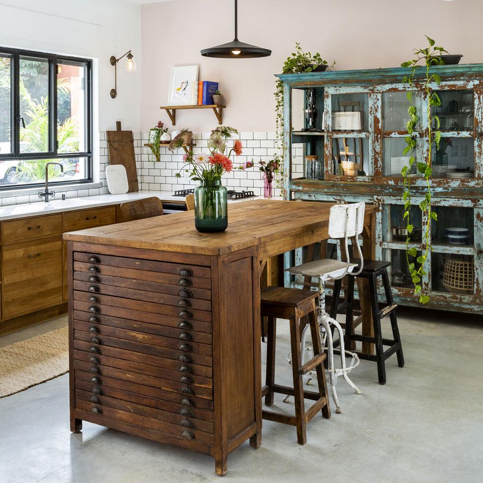 המטבח תוכנן סביב ארון הוויטרינה הירקרק, שסומן עבורו מראש, והאי מבוסס על משטח עץ גושני, שהורכב על ארונית מגירות ישנה (צילום: בועז לביא)