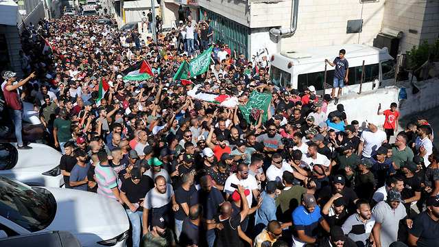 נקבר הפלסטיני שנורה למוות על ידי שוטרים בעיסאוויה, רעולי פנים שיגרו זיקוקים (צילום: AP)