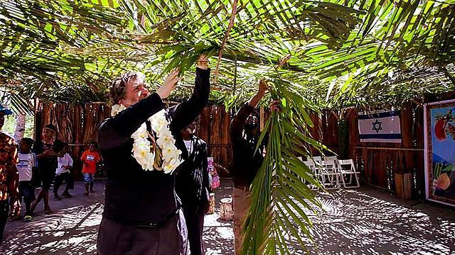 הרב טוביה סינגר בונה סוכה באינדונזיה (קרדיט: באדיבות הרב טוביה סינגר והרב אליהו בירנבוים )
