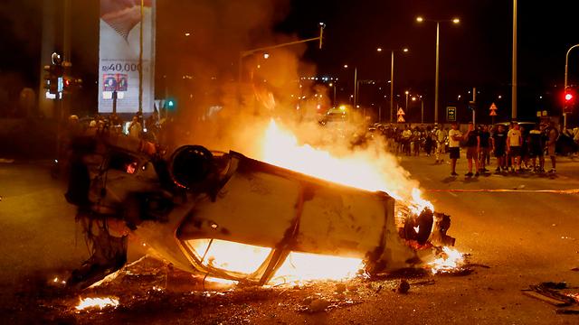 Машина, подожженная участниками беспорядков в Тель-Авиве. Фото: AFP