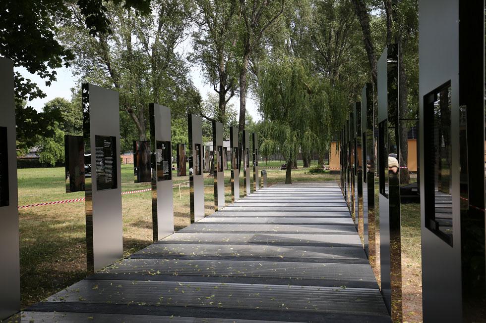 צועדים בשביל מחוץ למחנה אושוויץ, על מה שעשוי להזכיר פסי רכבת או את מדי האסירים (צילום: Jakub Wlodek)