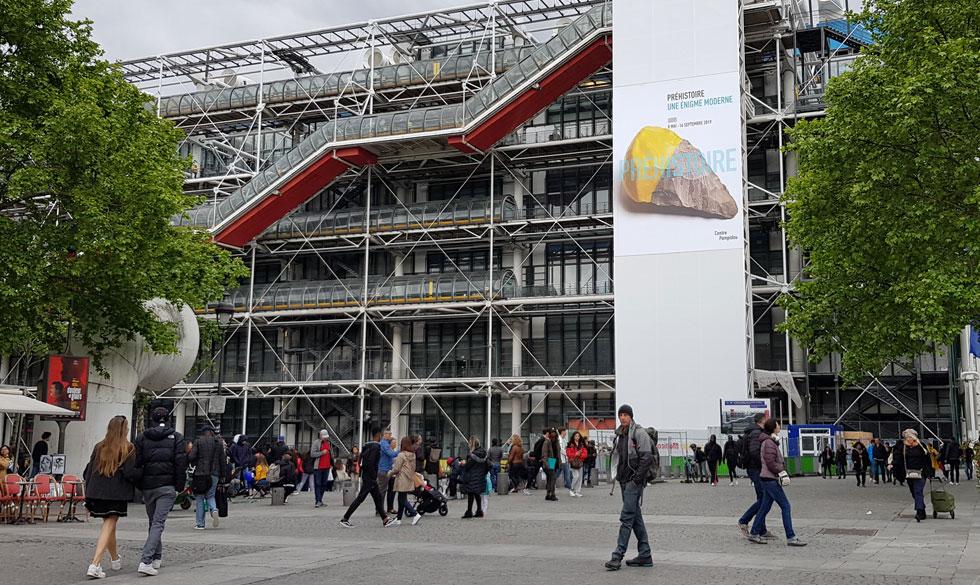 דב גנשרוא ברחבה שלפני מרכז פומפידו. מאחוריו השלט העצום שעליו אבן צור טבולה בגומי צהוב, אחת מסדרת ''אבני צור'', שעליה עבד עם דרך בשנים 2010-2012 (צילום: ורד אליעזרי גנשרוא)