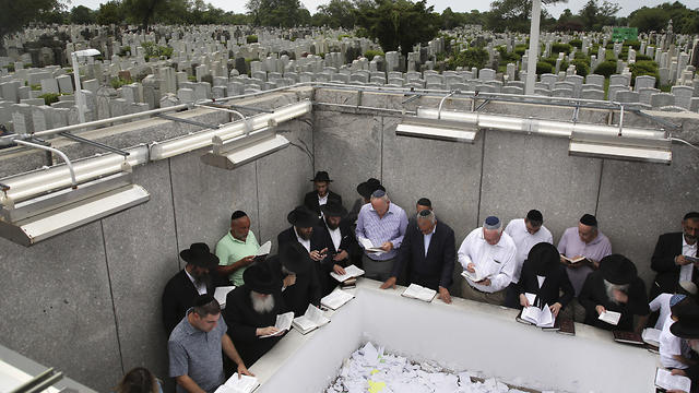 People pray at the gravesite of Rabbi Menachem M. Schneerson in the Queens borough of New York. July 2, 2019