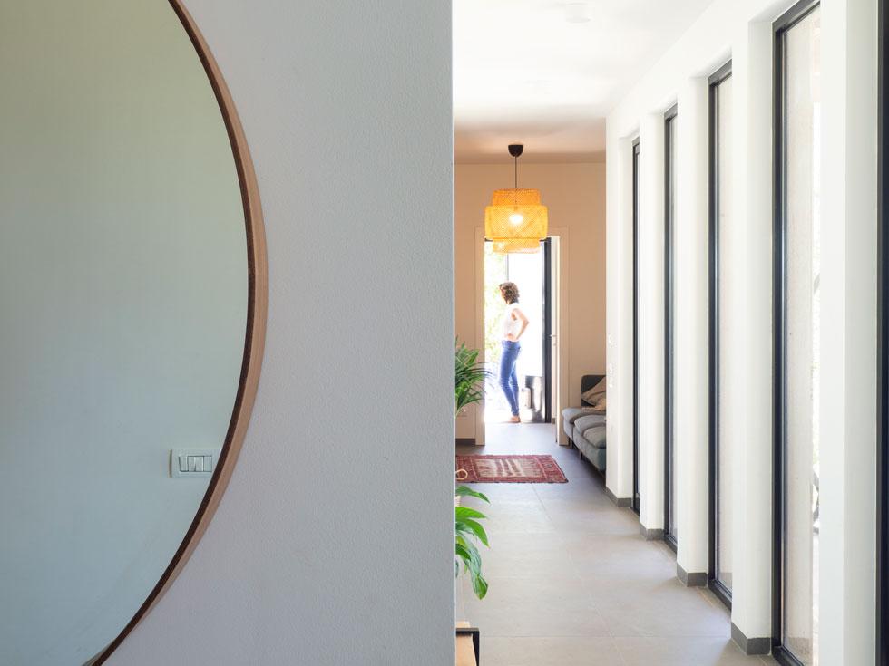 לצד המסדרון הארוך המלווה את חדרי הילדים תוכננה שרשרת של חלונות הנפתחים אל הנוף לכל גובה הקיר. ''זה מסדרון שקורים בו דברים. נישות, חלונות. בכל פעם שיוצאים מאחד החדרים רואים את הנוף''. בקצה פינת משפחה וצפייה בטלוויזיה, חדר כביסה ויציאה למרפסת שירות שבה גם מקלחת חוץ (צילום: נגה שחם פורת)