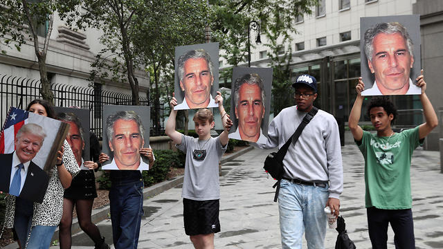 Demonstrators hold signs aloft protesting Jeffrey Epstein, as he awaits arraignment in the Southern District of New York, July 8, 2019