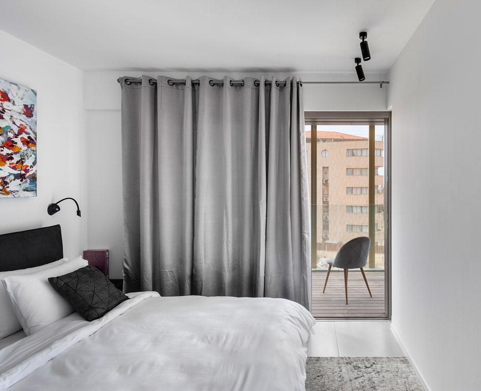 אחד משני חדרי השינה. הדירה עוצבה בלבן, אפור ושחור, כשאת הצבע מוסיפים חפצי הנוי וציורי השמן על הקירות (צילום: עודד סמדר)
