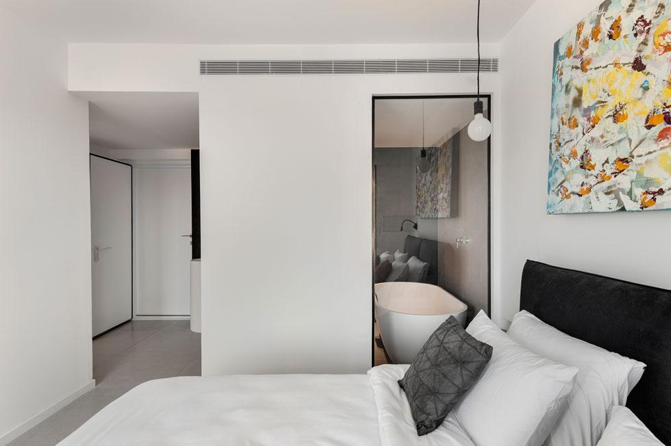 """קיר זכוכית מפריד בין אזור השינה לאמבטיה, """"כדי שיהיה ניתן לראות ממנה את הים"""", מסבירה המעצבת מיכל האן (צילום: עודד סמדר)"""