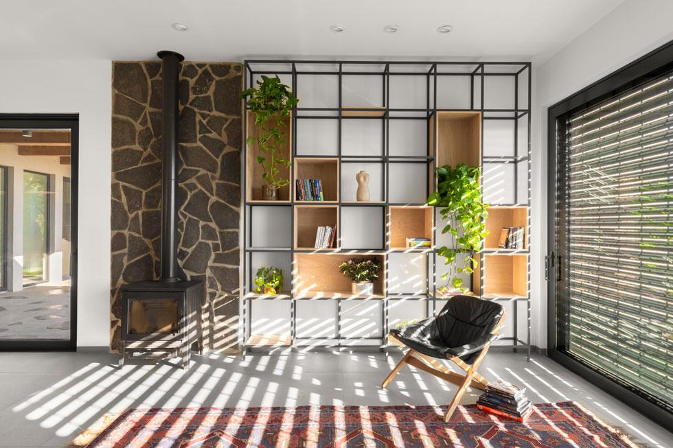 ספריית ברזל ועץ לצד קיר אבני הבזלת (צילום: טל ניסים)