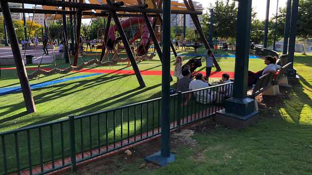Visitors enjoy a children's playground at a park in the northern Israeli town of Afula, July 13, 2019