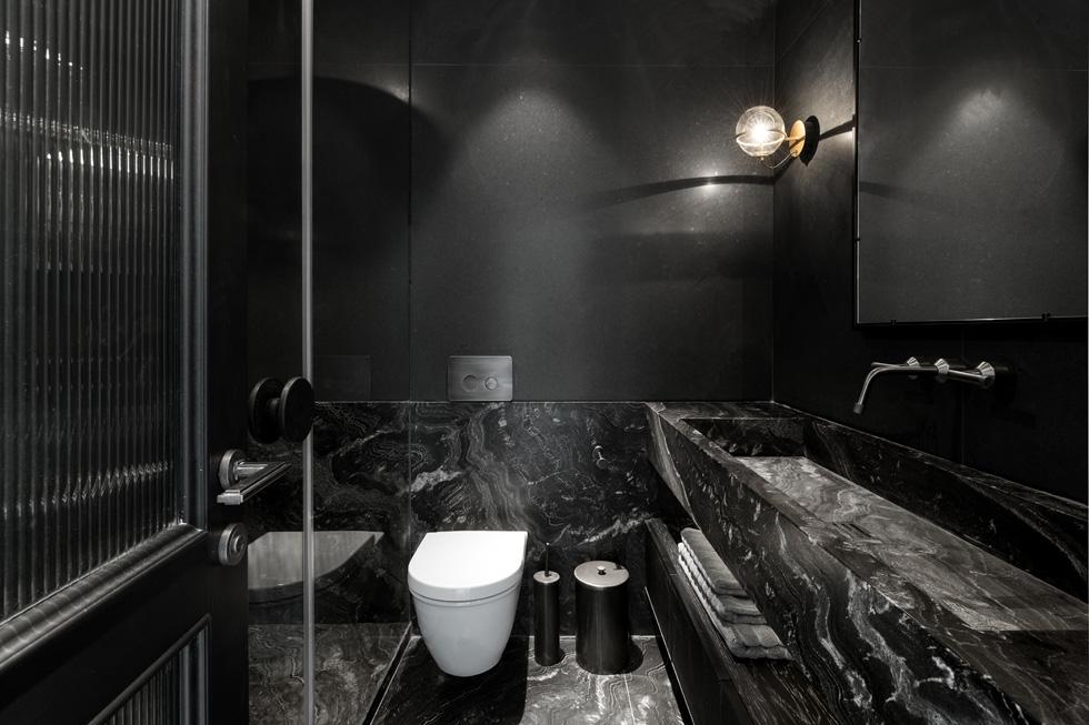 חדר הרחצה הצמוד לחדר האורחים מחופה באבן טבעית כהה ודרמטית (צילום: גדעון לוין)