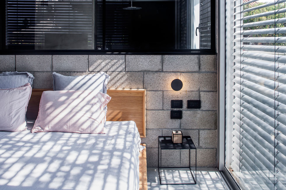 שיטת הבנייה כאן קלה, והפנים עוצב בסגנון תעשייתי. החלון שמעל המיטה פונה לחדר הרחצה הצמוד. עיצוב: רוני קרן. לחצו לכתבה המלאה (צילום: יואב גורין)