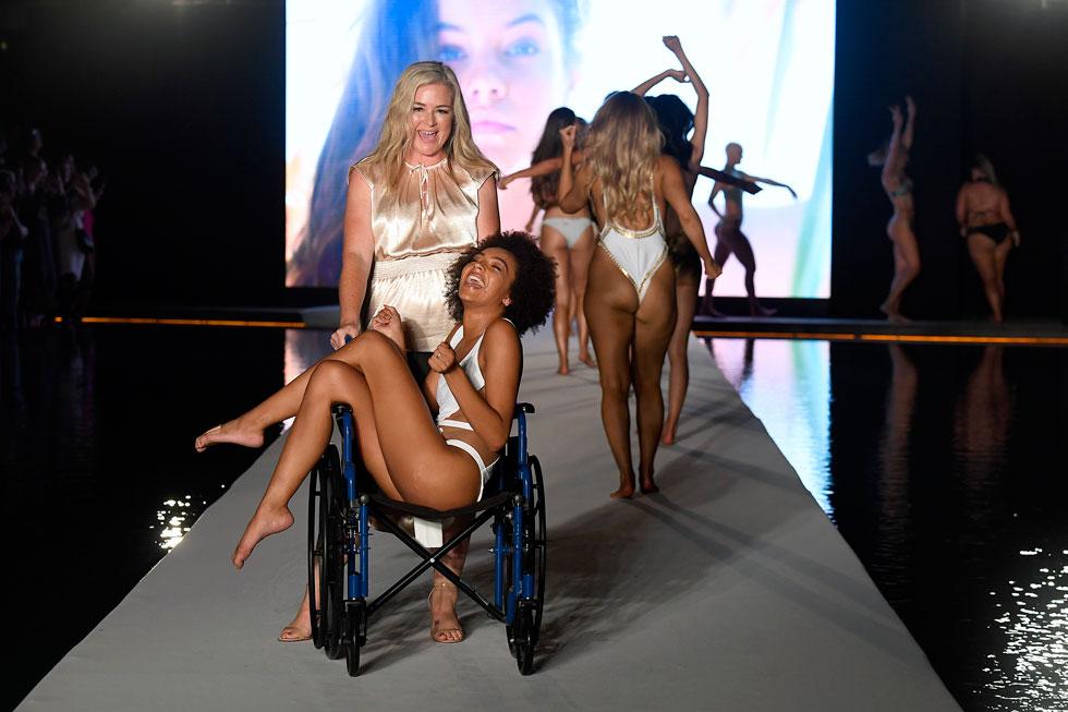 הדוגמנית והרקדנית דג'ניאל קארטר, שנפגעה בשתי רגליה, לא נתנה לפציעתה לחבל בתשוקתה להופיע על המסלול. היא אומנם לא יכולה לצעוד, אבל כן לעמוד, אז היא הובלה אל הצלמים בכיסא גלגלים (צילום: Frazer Harrison/GettyimagesIL)