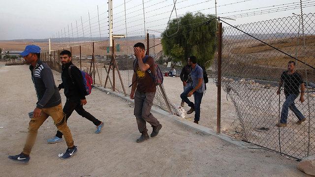 פועלים פלסטינים נכנסים לישראל דרך פרצה ב גדר ליד חברון (צילום: AFP)