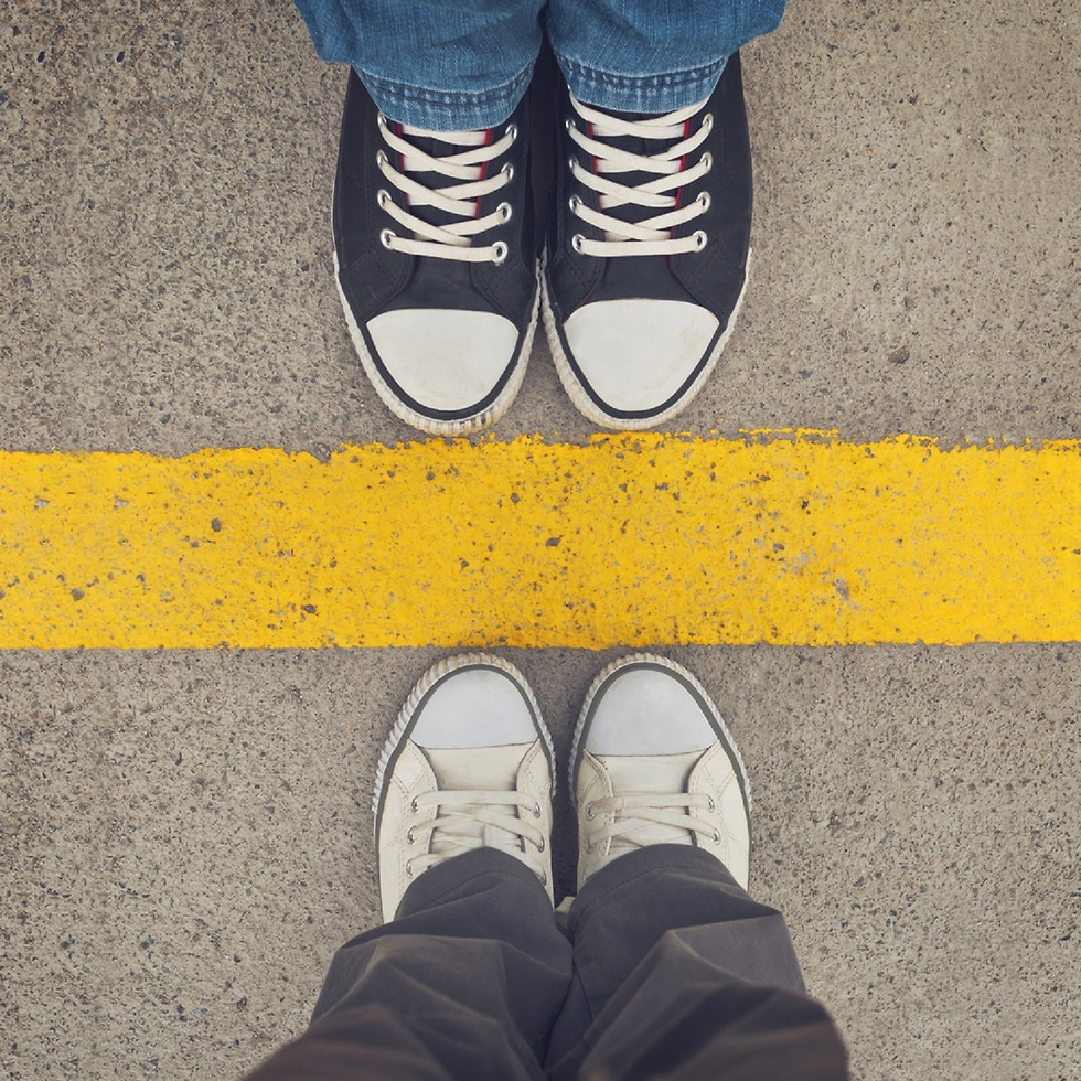 שני זוגות נעליים ברגליים אחד מול השני עם קן צהוב באמצע ()