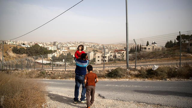 Ismail Odeideh walks with two of his children in Sur Baher
